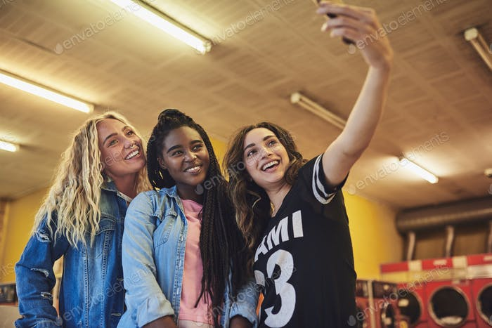 Smiling female friends standing together in a laundromat taking selfies