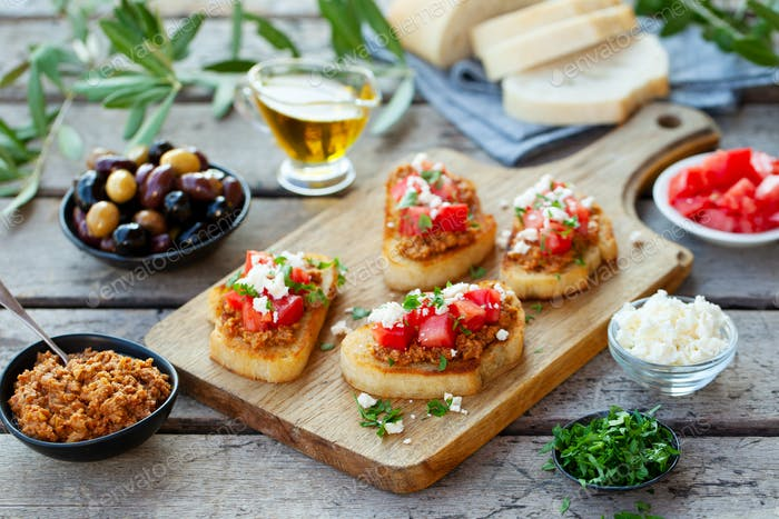 Bruschetta With Olive Tapenade and Fresh Tomatoes on Cutting Board. Wooden Background.