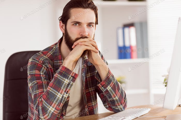 Hipster businessman sitting at his desk in his office