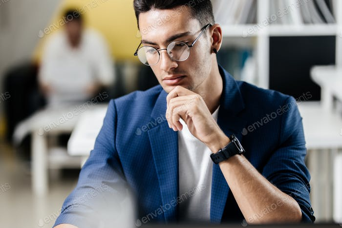 Professional young architect in glasses dressed in blue checkered jacket works on the laptop in the