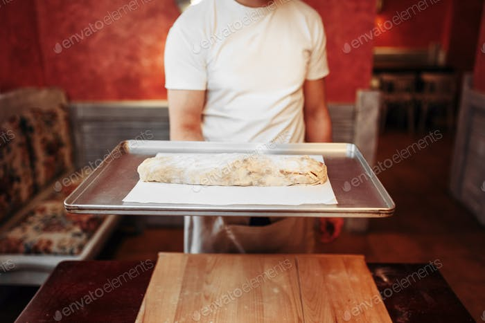 Chef holds metal baking sheet with apple strudel