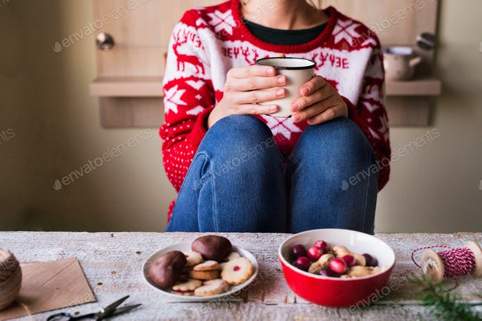 Unrecognizable woman drinking coffee at Christmas time.