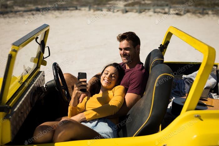 Happy caucasian couple sitting in beach buggy by the sea relaxing