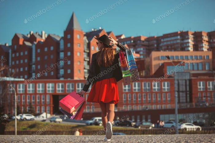 The girl walking with shopping on city streets