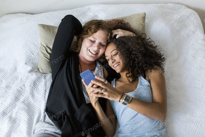Two women lying down on bed and using smart phone