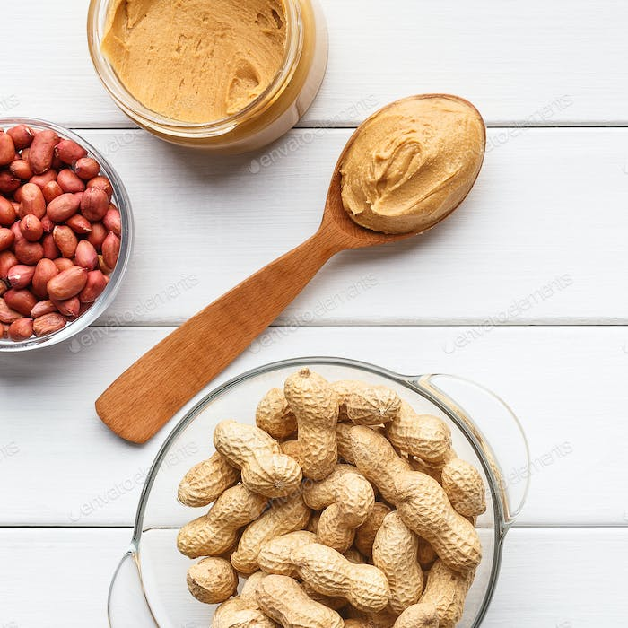 Bowls with peanuts and jar of peanut butter