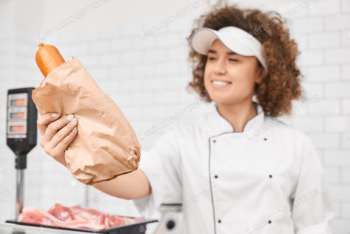 Female butcher giving sausages from counter
