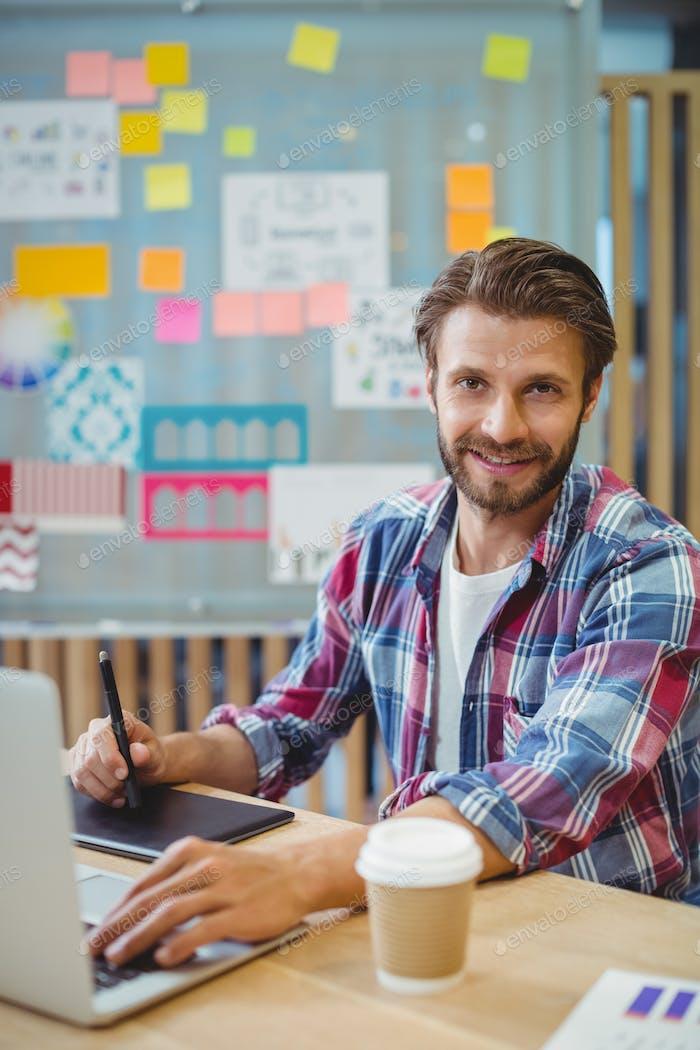 Retrato del diseñador gráfico feliz usando computadora portátil y tableta gráfica
