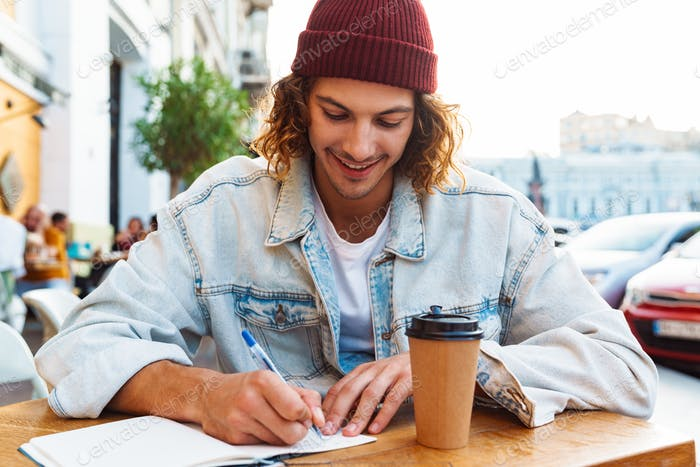 Attractive young hipster man writing notes