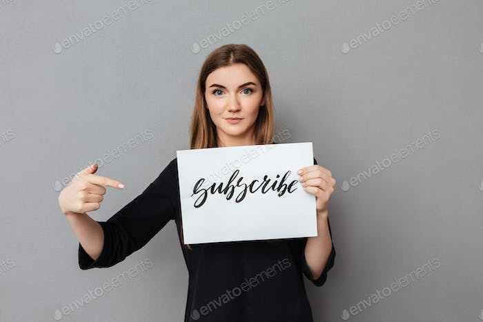 Portrait of beautiful lady standing and holding postcard while dreamily looking in camera