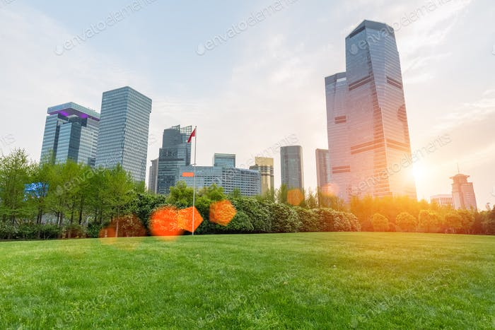 city park lawn with modern building in sunset