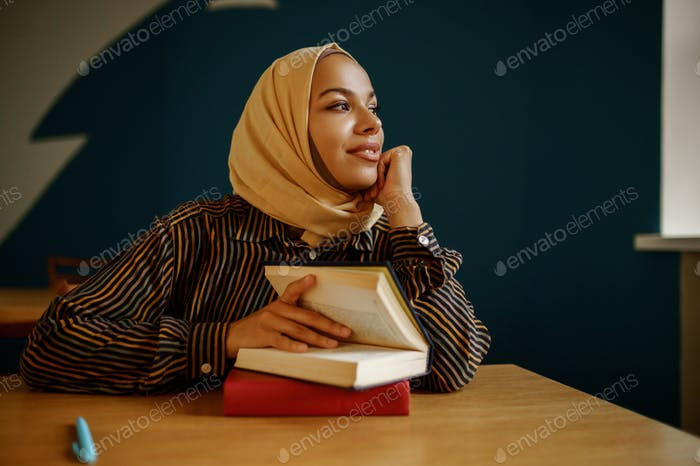 Arab female student in hijab holds textbook