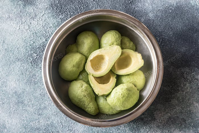Halved avocados in the metal bowl