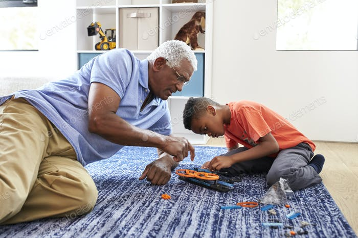 Grandfather With Grandson Lying On Rug At Home Building Robotic Model Together