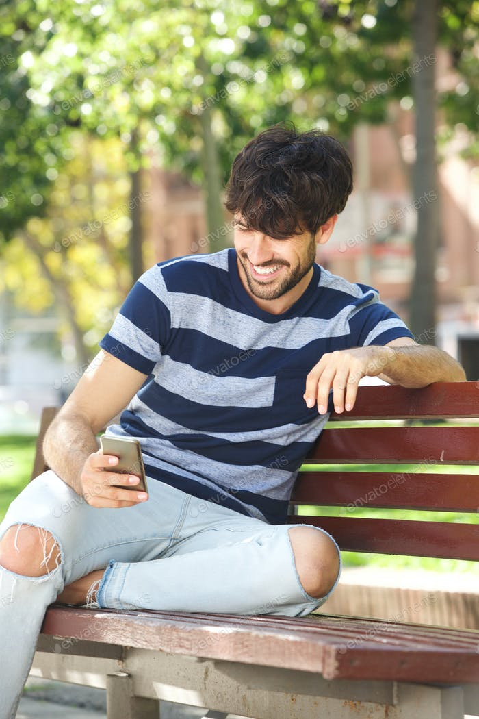 young man smiling with cell phone in park