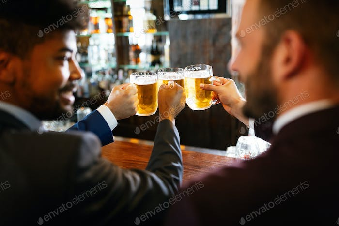 People, men, leisure, friendship and celebration concept. Happy male friends drinking beer at pub