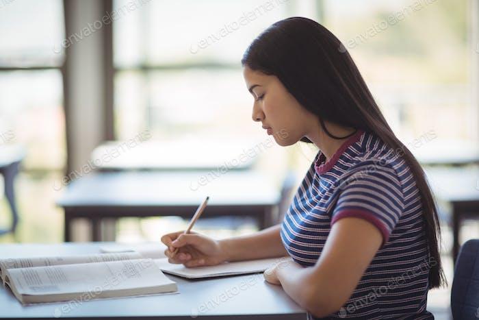 Attentive schoolgirl studying in classroom