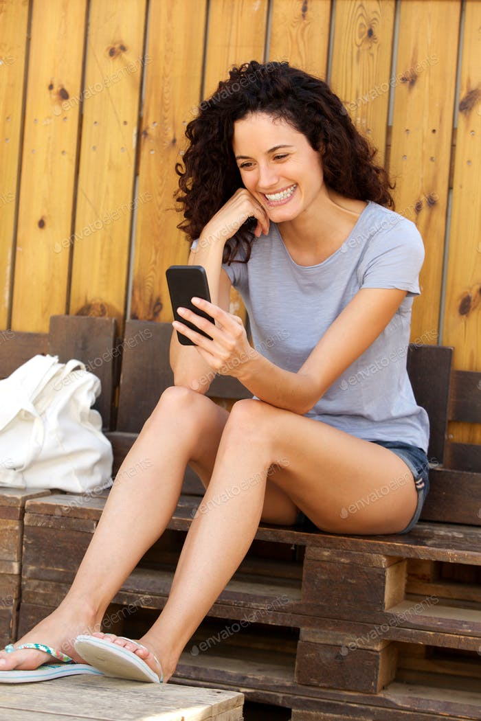 smiling young woman looking at cellphone