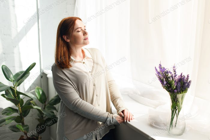 beautiful girl standing near window with closed eyes at home