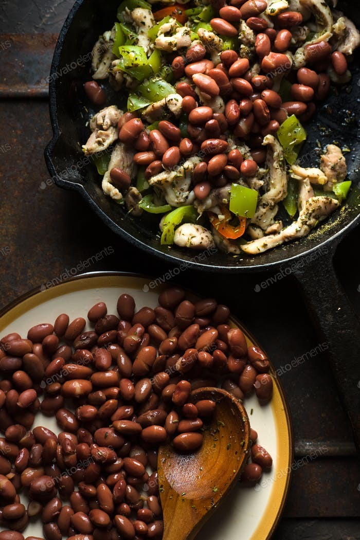 Beans are spread in a frying pan with pepper and chicken top view