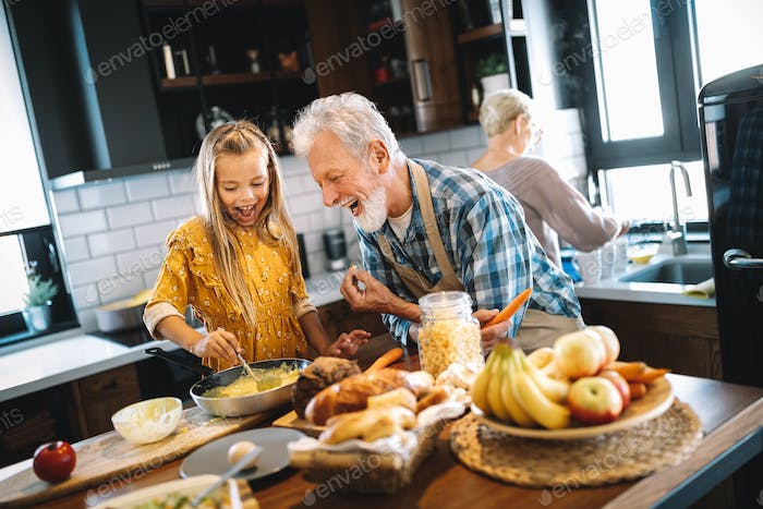 Smiling grandparents having breakfast with their granddaughter