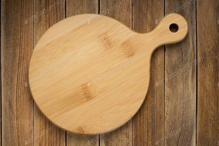 cutting board at rustic wooden plank background