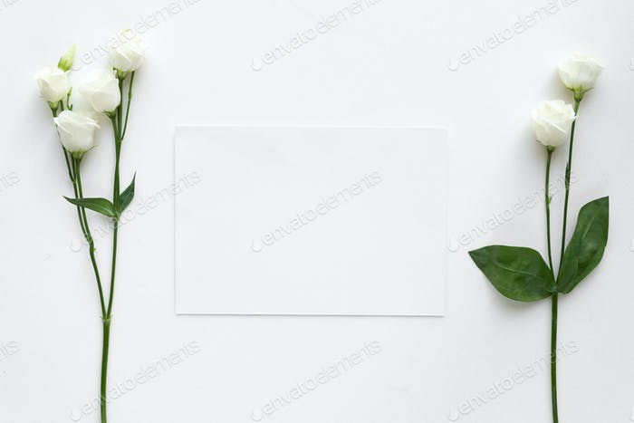 Wedding invitation card with roses, on white marble. Top view.