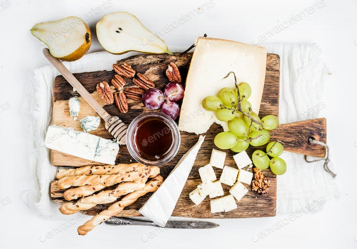 Cheese appetizer set. Various types of cheese, honey, grapes, pear, nuts and bread grissini sticks