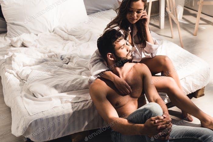 shirtless man sitting near bed while girl sitting in bed and looking at guy