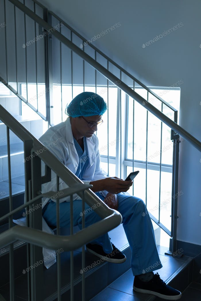 Side view of Caucasian male surgeon using mobile phone while sitting on stairs at hospital