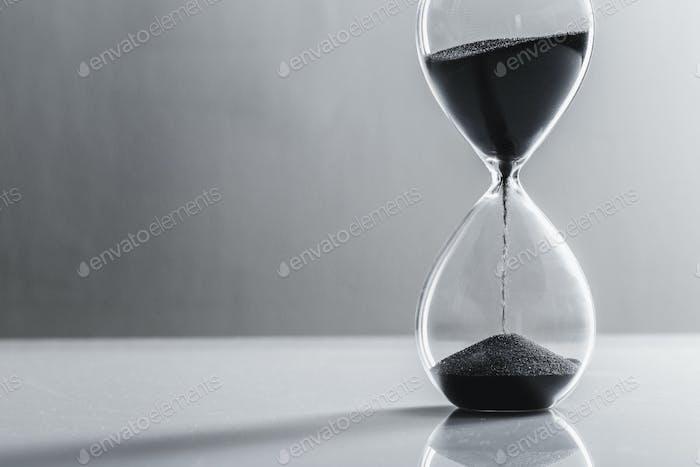 Крупным планом песочные часы на столе. Крупным планом