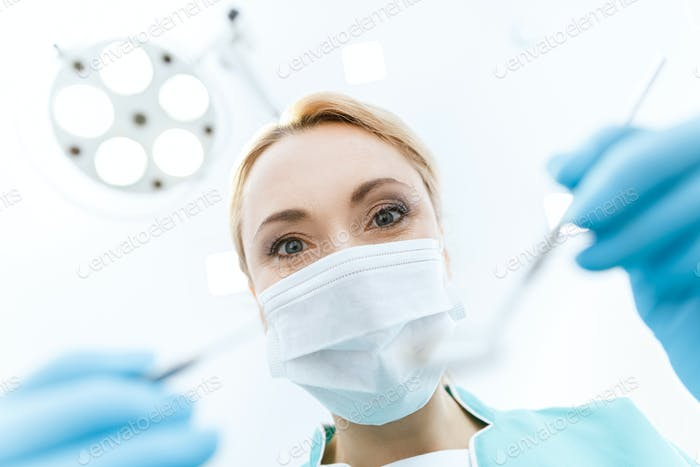 Professional dentist in medical mask working in clinic and looking at camera