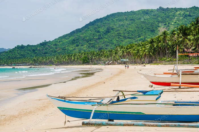 Local boats on Nacpan Beach on sunny day. El Nido, Palawan, Philippines