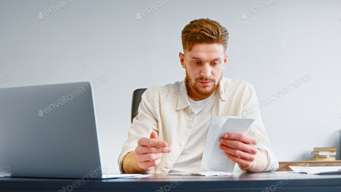 Bearded professional accountant sorts paper invoice receipts sitting at table with white laptop