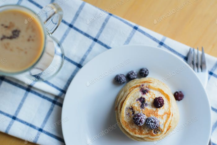 fritter or oladyi with blackberry, frozen berries on plate, fork and coffee