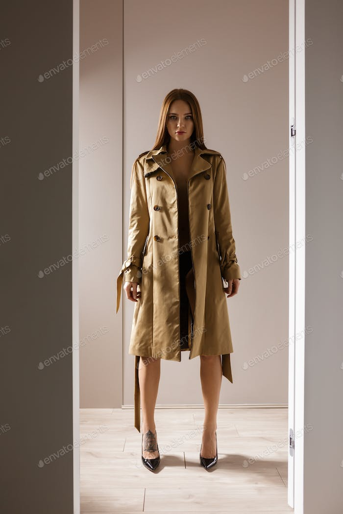 Portrait of beautiful lady in trench coat and lingerie and black shoes on heels standing doorway