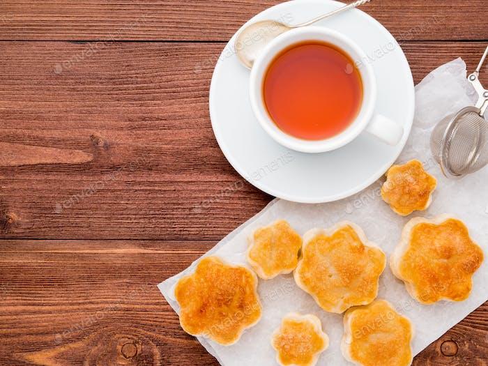 Frühstück mit Hausbacken und einer Tasse Tee auf braunem Holztisch, Draufsicht