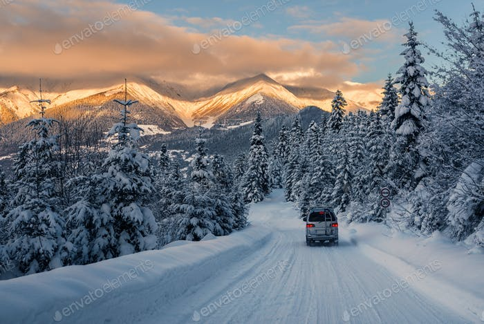 the car is riding on the powder snow road in the mountains