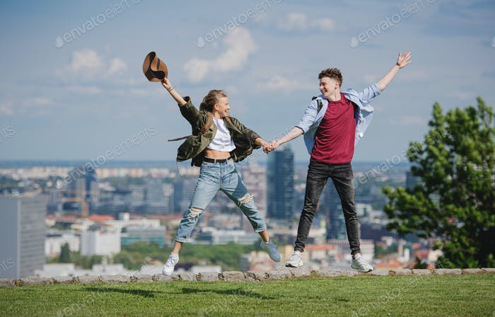 Cheerful young couple travelers in city on holiday, jumping. Cityscape in the background
