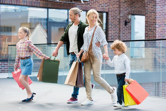 parents and little kids walking with shopping bags in mall