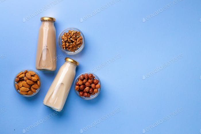 Bottles of vegan non dairy milk with various nuts on blue background