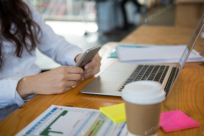 Female business executive using mobile phone