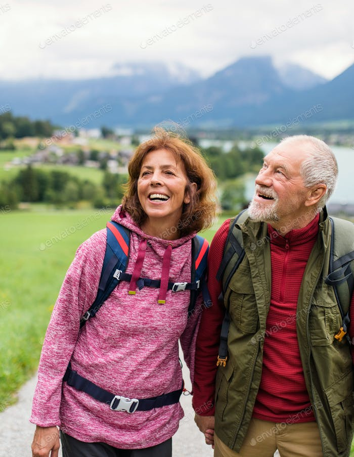Front view of senior pensioner couple hiking in nature, talking.