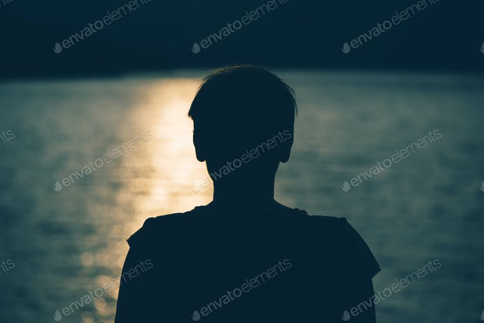 Thumbnail for Silhouette of depressed sad woman standing by the lake