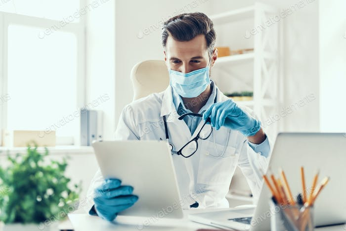 Busy young man in white lab coat