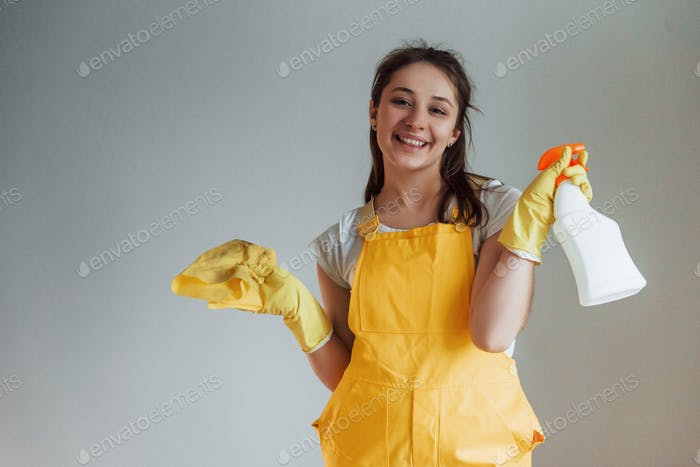 Housewife in yellow uniform standing with cleaning spray for windows indoors