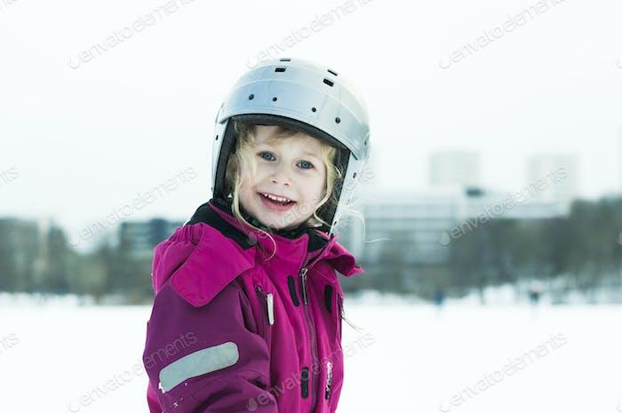Portrait of smiling girl (4-5) in helmet