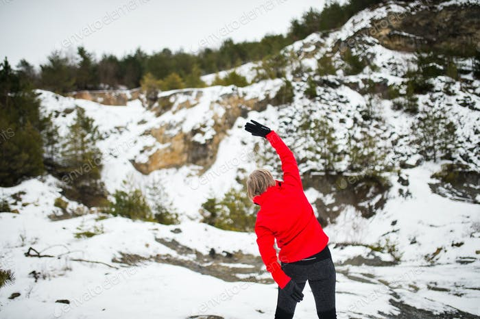 Senior woman jogging in winter nature.
