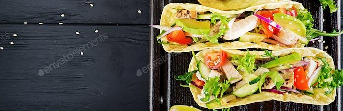 Mexikanische Tacos mit Hühnerfleisch, Avocado, Tomaten, Gurke und r