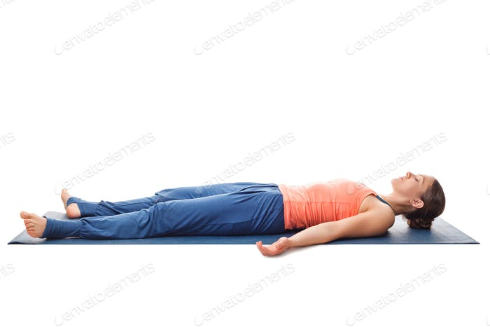 Sporty fit yogi girl relax in yoga asana Savasana